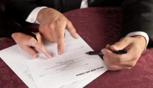 Старый человек подписывает у нотариуса свою квартиру в пользу государства